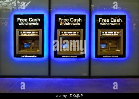 La gare s'allume en bleu autour de la rangée de trous d'argent du distributeur automatique de billets Dans le mur distributeur d'argent machine Kings Cross train Station Londres Angleterre Royaume-Uni