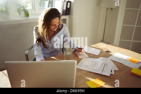 Jolie jeune femme à écrire des notes de sourire. Beau portrait de femmes travaillant à la maison. Banque D'Images