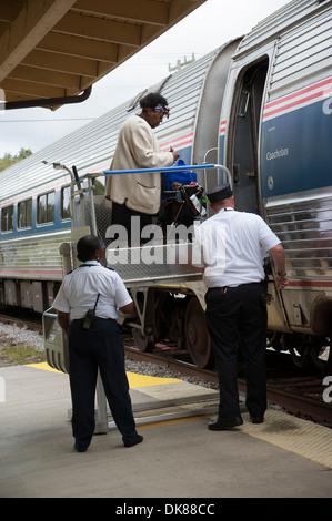Dame au moyen d'un élévateur de fauteuil roulant à bord d'un train à la gare Amtrak DeLand Florida USA Banque D'Images