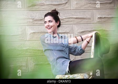 Jeune femme assise sur une chaise à l'extérieur Banque D'Images