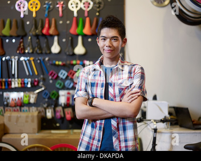 Portrait de jeune homme en bike shop with arms folded Banque D'Images