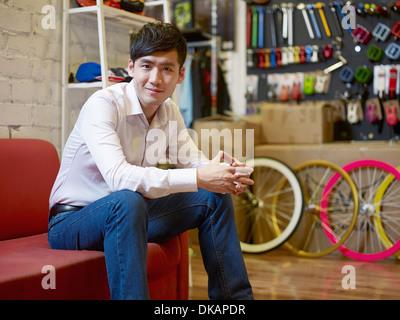 Portrait de jeune homme assis dans bike shop Banque D'Images