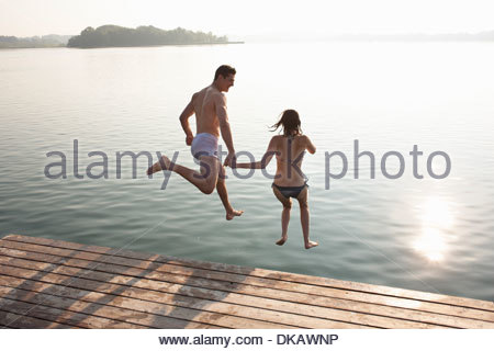 Jeune couple Jumping off lake pier Banque D'Images