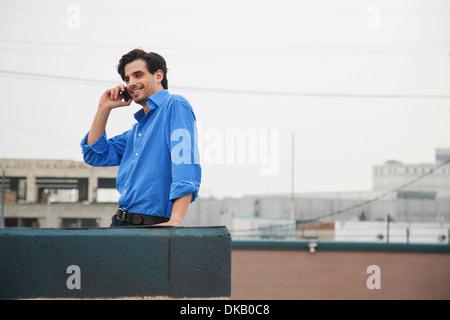 Jeune homme confiant à l'aide de mobile sur les toits de la ville Banque D'Images