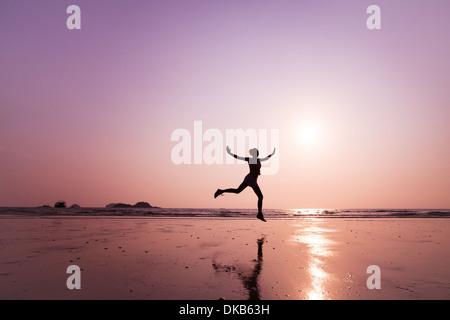 Jeune femme sautant sur la plage Banque D'Images