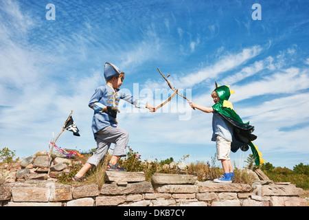 Deux garçons déguisés jouer avec des bâtons de combat, Eggergrund, Suède Banque D'Images