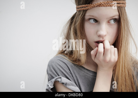 Portrait of Girl wearing tresse cuir autour de tête, holding feather, finger in mouth Banque D'Images