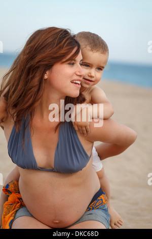 Mère enceinte donnant tout-petit piggy back Banque D'Images