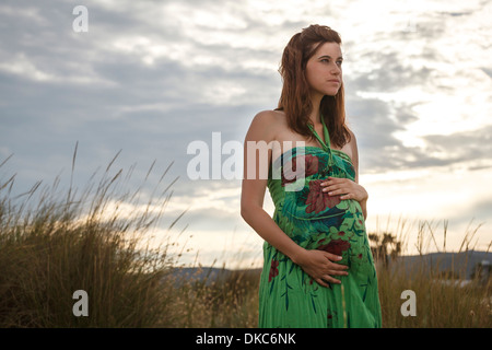 Pregnant woman standing in field Banque D'Images