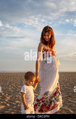Mère et enfant en marchant le long de la plage, main dans la main Banque D'Images