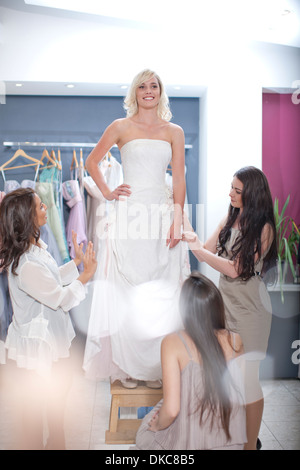 Young woman trying on robe de mariage, avec des amis Banque D'Images