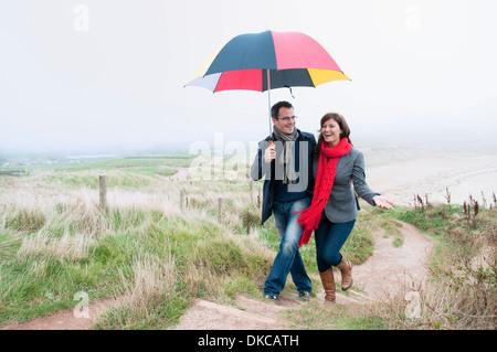 Couple sur la côte à pied portant un parapluie, Thurlestone, Devon, UK Banque D'Images