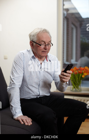 Senior man at home texting on mobile phone Banque D'Images