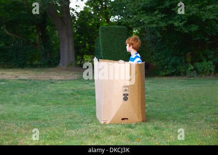 Jeune garçon regarder à partir de la boîte de carton dans le jardin Banque D'Images