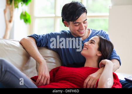 Jeune couple reclining on salon canapé