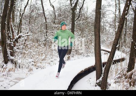 Femme d'exécution sur une allée de la forêt en hiver Banque D'Images