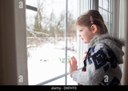 Jeune fille à la fenêtre de la neige dans le jardin à Banque D'Images
