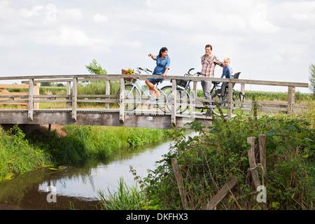 Plus de famille à vélo du pont de bois Banque D'Images