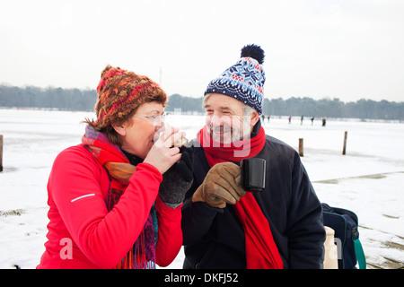 Couple having boisson chaude dans la neige