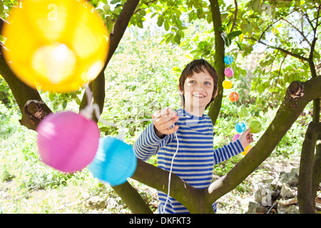 Boy putting fairy lights in tree Banque D'Images