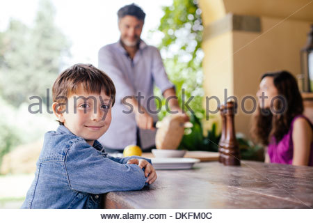 Garçon à table avec père et sa sœur en arrière-plan Banque D'Images