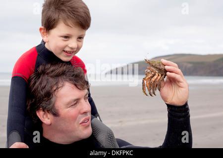 Père holding crab avec fils Banque D'Images