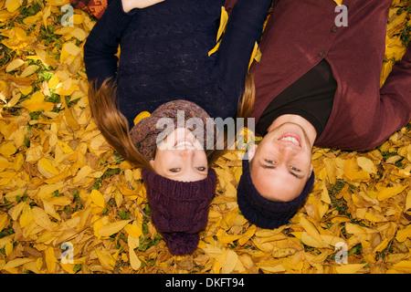 Jeune couple couché dans les feuilles d'automne Banque D'Images