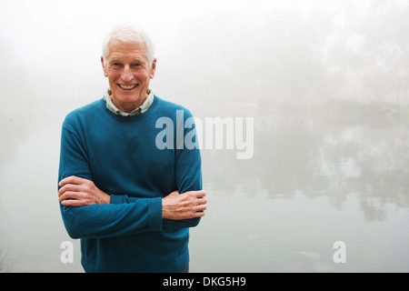 Senior man with arms crossed par foggy lake Banque D'Images