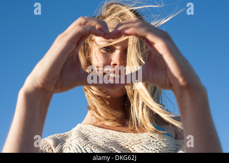 Portrait of young woman making heart sign, Breezy Point, Queens, New York, USA Banque D'Images