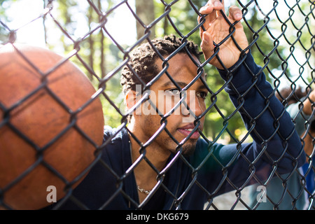 Portrait of young man holding basketball par wire fence Banque D'Images