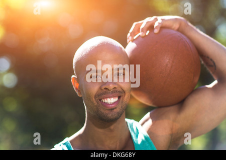 Portrait of young man holding basketball Banque D'Images