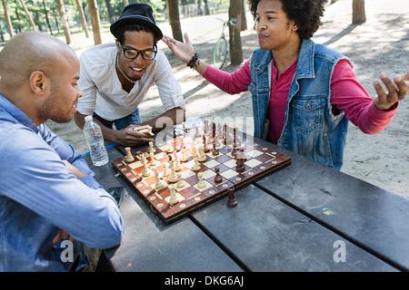 Trois jeunes hommes jouant aux échecs dans le parc Banque D'Images