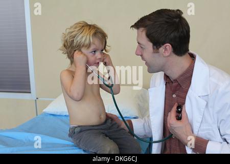 Jeune homme médecin en clinique partager stéthoscope avec boy Banque D'Images
