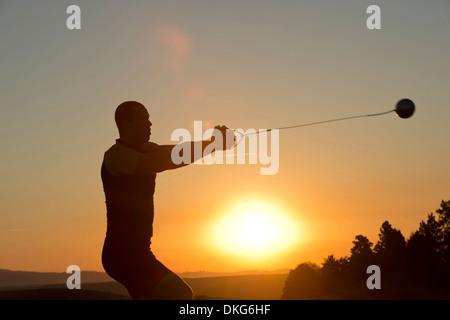 Jeune homme se préparent à lancer le marteau au coucher du soleil Banque D'Images