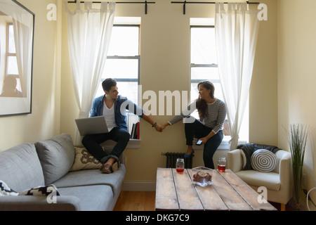 Jeune couple assis sur le rebord de fenêtre, holding hands Banque D'Images