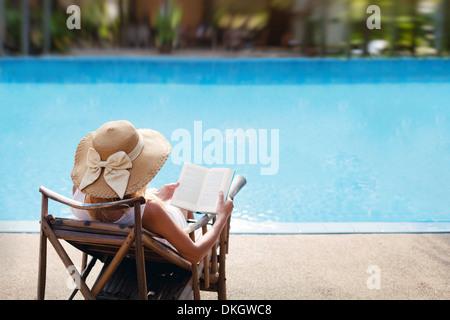 Femme lisant et relaxant près de piscine de luxe Banque D'Images