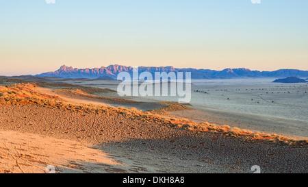 La première lumière sur les dunes et les montagnes de NamibRand, Désert du Namib, Namibie, Afrique Banque D'Images
