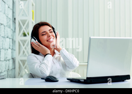 Young cheerful businesswoman listening music in headphones at office Banque D'Images