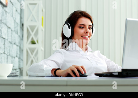 Young businesswoman in headphones working on a laptop at office Banque D'Images