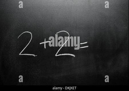Un tableau noir avec la somme 2+2= écrit dessus en blanc craie. Banque D'Images