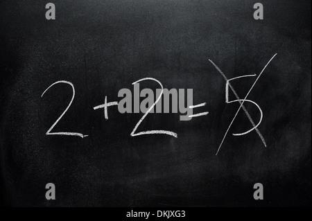 Un tableau noir avec la somme 2+2=5 écrit dessus en blanc craie. Banque D'Images