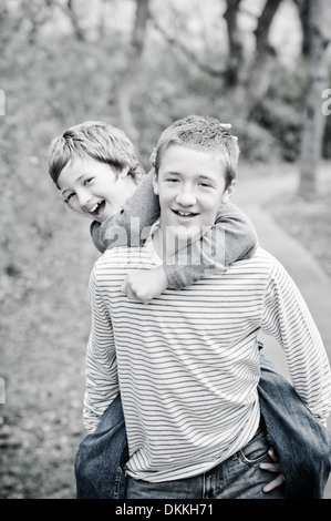 Frères mignon, teen boy giving piggyback ride en plein air, s'amusant - noir et blanc Banque D'Images
