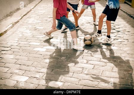 Enfants jouant avec ballon de soccer sur la rue pavée Banque D'Images