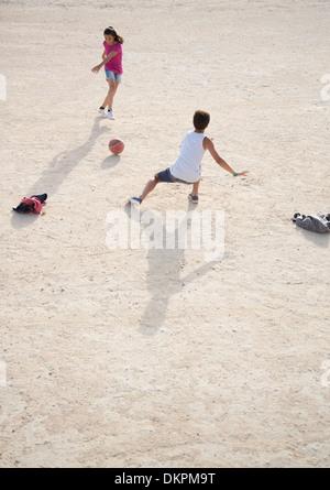 Enfants jouant avec un ballon de soccer dans le sable Banque D'Images