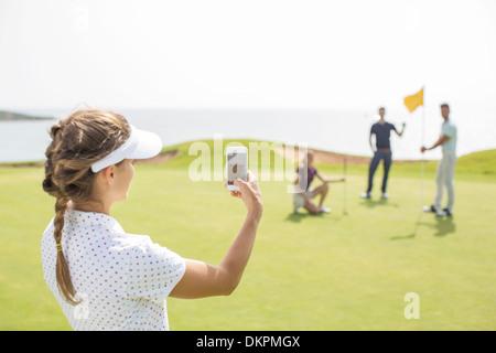 Femme photographiant les amis on golf course Banque D'Images