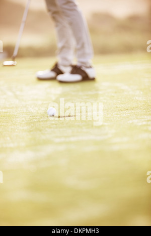 Man putting on golf course Banque D'Images