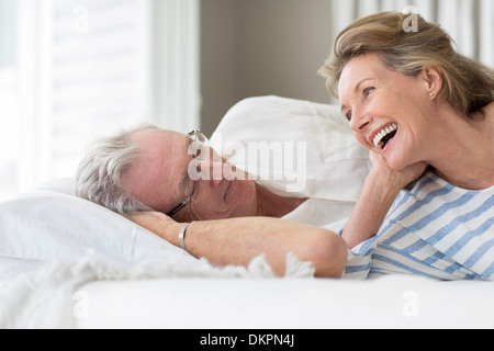 Vieux couple relaxing on bed Banque D'Images