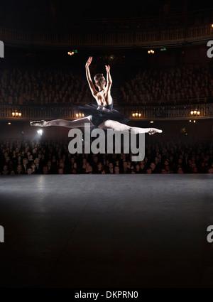 Ballerine mid-air sur scène de théâtre Banque D'Images