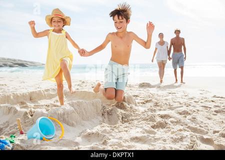 Enfoncer les enfants sandcastle on beach Banque D'Images