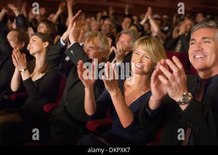 Public enthousiaste des mains dans le théâtre Banque D'Images